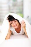 Fun woman duvet. Fun middle aged woman lying under duvet laughing Stock Image