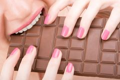 Fun woman eating chocolate Stock Images