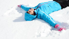 Fun woman liying down in snow Royalty Free Stock Photos