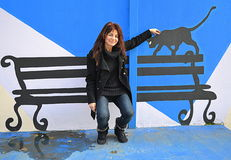 Fun woman painted bench black cat. Smiling woman facetiously sitting on painted on the wall bench and caressing the black cat who walks on the bench edge stock photography