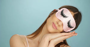 Fun woman relaxing in a sleep mask. Fun woman relaxing in a pink feminine sleep mask decorated with long eyelashes resting her tilted head on her hands , over stock photography