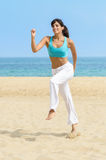 Fun woman running jumping on beach Stock Photo