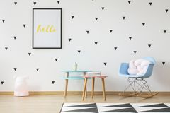 Fun wooden tables, light pink pillow in a baby blue rocking chair and a toy lamp in a cute nursery room interior with triangle st. Ickers on a white wall stock images