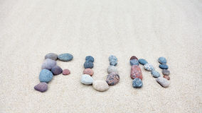 Fun word made of pebbles on a sandy beach Stock Photography