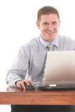 Fun at work. Smiling businessman working on the laptop on his desk Royalty Free Stock Image