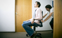 Fun at work. Two employees have fun at work, in a chair race Stock Images