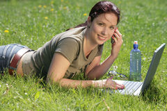 Fun working - technology in the park. Girl laying in the grass while working on her notebook Stock Images