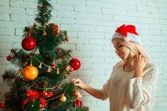 Fun young blonde decorates a christmas tree in santa hat royalty free stock image