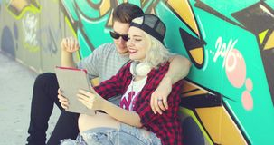 Fun young couple waving at a tablet pc. During a video conferencing as they cuddle together on the sidewalk in front of colorful graffiti on a concrete wall stock video