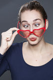Fun young girl with heart-shape glasses for cool vision of love Royalty Free Stock Photos