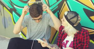 Fun young hipster couple listening to music. On a mobile phone as they sit on the street in front of a colorful graffiti covered wall stock video footage