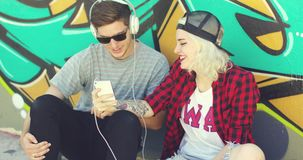 Fun young hipster couple listening to music. On a mobile phone as they sit on the street in front of a colorful graffiti covered wall stock video