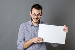 Fun young man holding a copy space banner to tease. Panel announcement - fun young man with eyeglasses and beard holding a copy space banner for teasing, gray Stock Photos