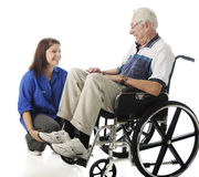 Fun for the Young and the Old. A teen volunteer and old men in a wheelchair talking and laughing together.  On a white background Stock Photos