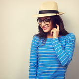 Fun young thinking woman looking down in glasses and straw hat. Stock Image