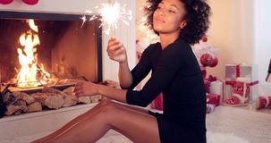 Fun young woman burning a sparkler for Christmas stock footage