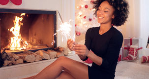 Fun young woman burning a sparkler for Christmas Royalty Free Stock Photo