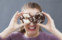 Fun young woman hiding eyes for disgust of fat sweets. Fun beautiful young woman hiding her eyes with chocolate and vanilla donuts for fear or disgust of fat and Stock Image