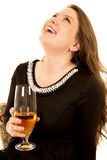 Fun young woman holding a wine glass looking up laughing Royalty Free Stock Images