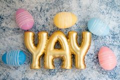 Fun youthful Easter egg background with the word YAY in gold lettering. Pretty pastel eggs.  royalty free stock images