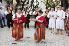 Funchal madeira - April 20, 2015: Aktörer med det färgrika och utarbetade dräktdeltagandet i ståta av blommafestivalen på Royaltyfri Bild