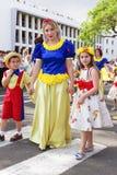 Funchal madeira - April 20, 2015: Kvinnan och barn med färgrika blom- dräkter på madeiran blommar festival Royaltyfri Foto
