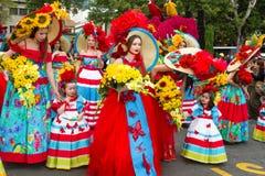 Funchal madeira - April 20, 2015: Unga kvinnor och barn med färgrika blom- dräkter på madeiran blommar festivalen, Funchal, Fotografering för Bildbyråer