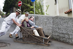 FUNCHAL, MADEIRA - MAY 20: Traditional downhill sledge trip on May 20, 2015 in Madeira, Portugal. Sledges were used as local trans. Traditional downhill sledge stock photography