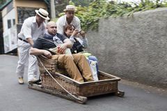 FUNCHAL, MADEIRA - MAY 20: Traditional downhill sledge trip on May 20, 2015 in Madeira, Portugal. Sledges were used as local trans. Traditional downhill sledge royalty free stock image