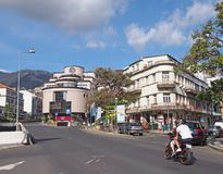 A main road in funchal city center with traffic and motorcycle with shops and people in the street. Funchal, madeira, portugal - 17 march 2109: a main road in royalty free stock images