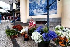 FUNCHAL, PORTUGAL - JUNI 29, 2015: Een traditionele vrouw verkoopt flo Stock Foto's