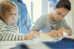 Funcionamento caucasiano da mulher quando sua imagem do desenho da filha perto dela Fotografia de Stock