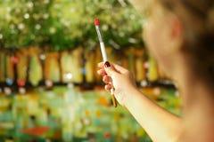 Funcionamento da jovem mulher como o pintor que estuda a composição que guarda o brus fotos de stock