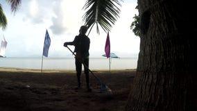 Funcionamento da jovem mulher como um líquido de limpeza da praia que ajunta as macas, restos no Sandy Beach tropical vídeos de arquivo