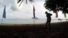 Funcionamento da jovem mulher como um líquido de limpeza da praia que ajunta as macas, restos no Sandy Beach tropical filme