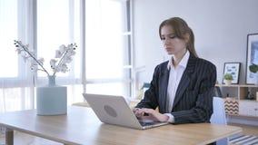 Funcionamento da jovem mulher, datilografando no portátil no escritório filme