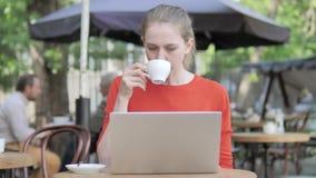 Funcionamento da jovem mulher no portátil e no café bebendo que sentam-se no terraço do café filme