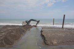 Funcionamento da máquina escavadora na praia para alisar a areia antes do começo da temporada de verão imagens de stock