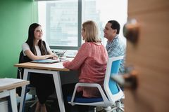 Funcionamento da mulher como o conselheiro de investimento que fala aos clientes no escritório fotografia de stock royalty free