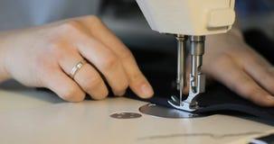 Funcionamento da mulher como o desenhador de moda com a máquina de costura no estúdio video estoque