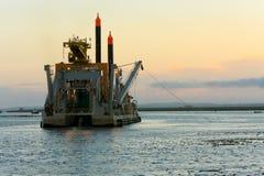 Funcionamento de dragagem da embarcação no por do sol. fotografia de stock royalty free