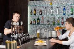 Funcionamento do empregado de bar quando um cliente beber no bar imagens de stock