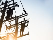 Funcionamento do homem da silhueta do trabalho do reparo do lineman da linha elétrica da eletricidade fotografia de stock