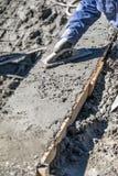 Funcionamento do trabalhador da constru??o da associa??o com o flutuador de madeira no concreto molhado foto de stock