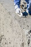 Funcionamento do trabalhador da constru??o da associa??o com o flutuador de madeira no concreto molhado imagem de stock