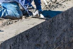 Funcionamento do trabalhador da constru??o da associa??o com o flutuador de madeira no concreto molhado imagens de stock royalty free