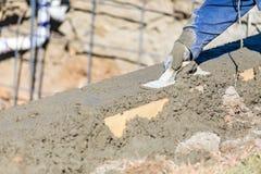 Funcionamento do trabalhador da constru??o da associa??o com o flutuador de madeira no concreto molhado fotos de stock