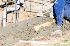 Funcionamento do trabalhador da constru??o da associa??o com o flutuador de madeira no concreto molhado fotos de stock royalty free