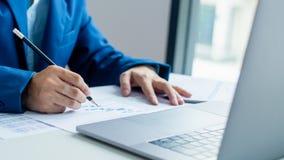 Funcionamento e análise do homem de negócios no portátil com documento financeiro imagens de stock
