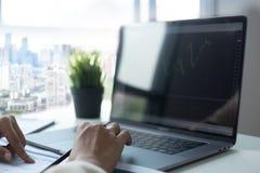 Funcionamento e análise do homem de negócios no portátil com financeiro fotografia de stock